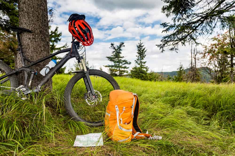 Bikepacking Niche Bike against a tree with backpack for camping by front wheel